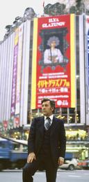 Илья Глазунов на фоне афиши его персональной выставки в Японии